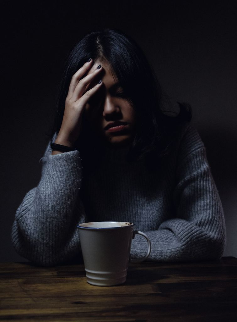 woman with anxiety with head in her hand
