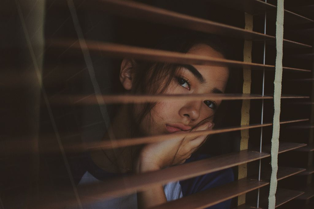 woman with anxiety looking out window